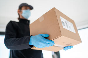 man delivering package with gloves and mask during COVID